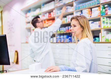 Two Friendly Pharmacists Working In A Drugstore.