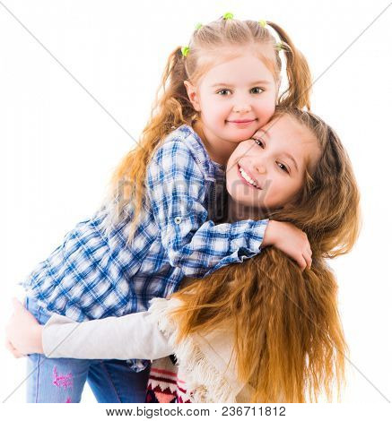 Two little girls sisters in casual clothes posing and hugging each other, isolated on white background