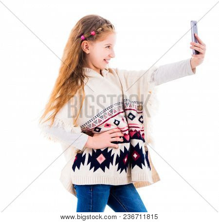 Teenage girl with long hair in poncho making a selfie isolated on white background. Girl taking pictures of herself using smartphone