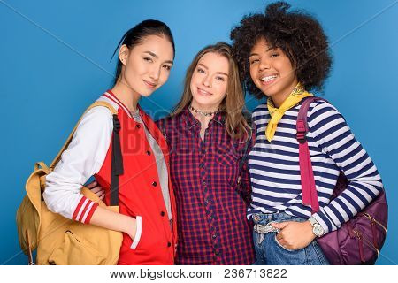 Female Multicultural Students Posing With Backpacks, Isolated On Blue
