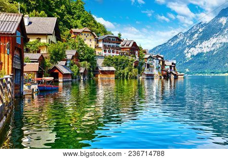 Hallstatt, Austria. View to Hallstattersee Lake and Alps mountains. Ancient houses at lake banks. Summer day. Blue sky with clouds.