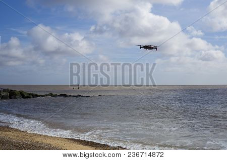 A Flying Drone Hovering Over A Beach