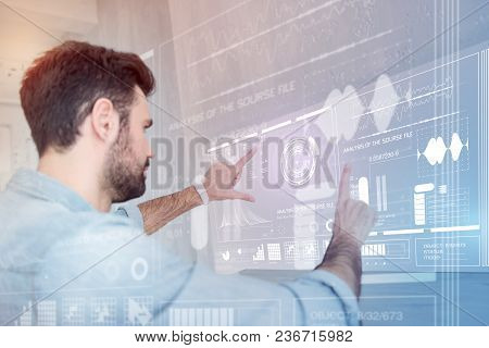 Careful Changes. Calm Clever Data Scientist Touching A Futuristic Transparent Screen While Working A
