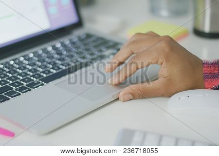 Crop anonymous woman working with laptop at table in office and browsing information in Internet using touchpad.