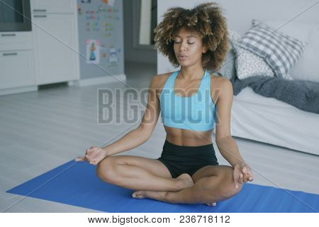 Fit ethnic woman in sportswear sitting on mat at home and meditating in yoga pose breathing and keeping eyes closed.