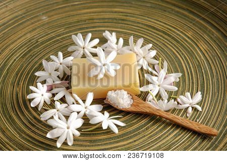 Spa Bath composition with lwhite flower, soap, salt in spoon on wooden bowl