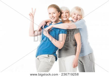 Mature Sportswoman Showing Peace Gesture While Two Senior Sportswomen Embracing Her Isolated On Whit