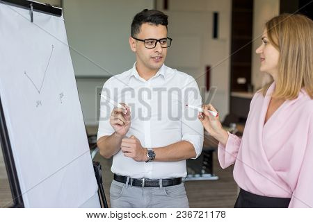 Smiling Male And Female Colleagues Discussing Strategy And Drawing Plan On Flipchart. Young Caucasia