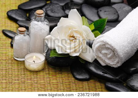 Spa setting with Gardenia flowers and candle,salt in bottle rolled ,pile stones towel on mat background