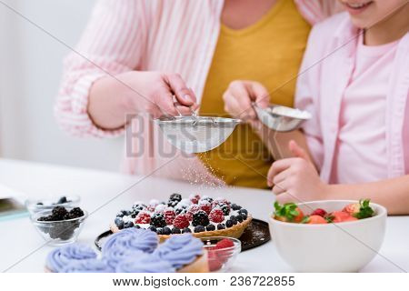 Cropped Shot Of Grandmother And Little Granddaughter Pouring Sugar Powder Onto Tart With Berries