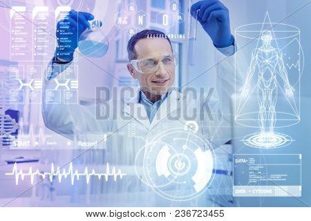 Great Results. Cheerful Clever Experienced Scientist Feeling Impressed While Holding The Bottles Wit