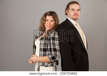 Elegant Couple Smiling For The Camera While Embracing. On Grey Background