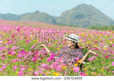 Traveler Asian Woman Relax And Freedom In Beautiful Blooming Cosmos Flower Garden.  Travel And Lifes