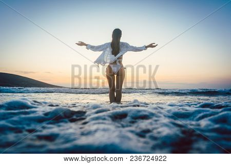 Woman enjoying the freedom of her vacation at the sea in a sunset mood