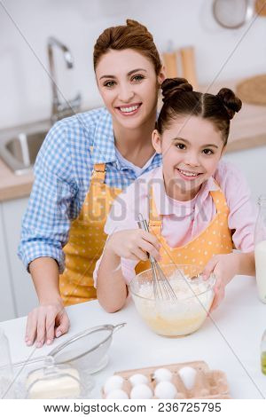 Young Happy Mother And Daughter Mixing Dough For Pastry At Kitchen