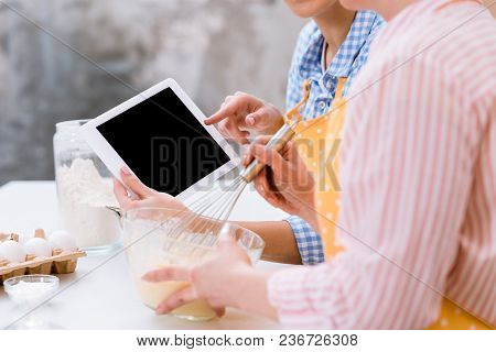 Cropped Shot Of Women Using Tablet Together At Kitchen While Cooking