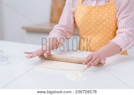 Cropped Shot Of Woman Rolling Dough For Pastry At Kitchen
