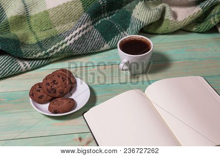 Cup With Hot Tea Or Coffee, Warm Plaid, Book On A Wooden Table. With Copy Space