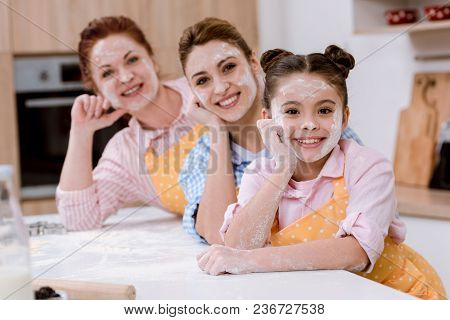 Three Generations Of Women In Aprons With Flour On Faces Standing In Row At Kitchen And Looking At C