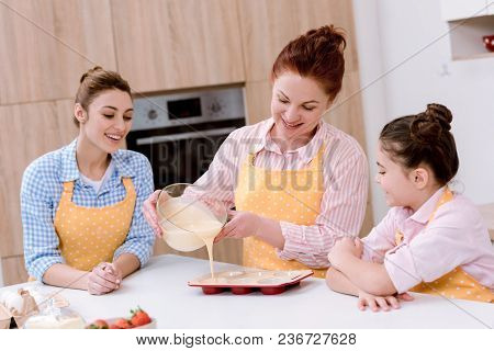 Three Generations Of Women Pouring Dough Into Baking Forms For Cupcakes At Kitchen