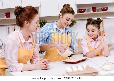 Three Generations Of Women Pouring Dough Into Baking Forms For Cupcakes At Kitchen Together