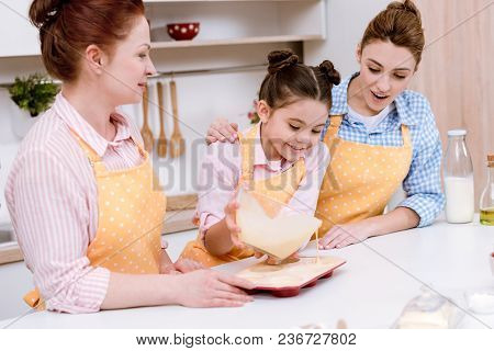 Three Generations Of Beautiful Women Pouring Dough Into Baking Forms For Cupcakes At Kitchen