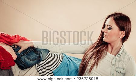 Lifestyle And Decisions About Outfit. Young Female Sit On Sofa Full Of Clothes. Woman With Stretched