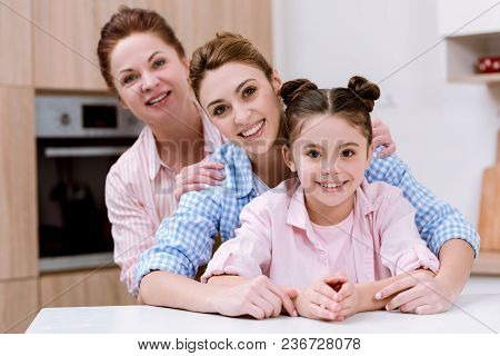Three Generations Of Women Standing In Row Together At Kitchen And Looking At Camera