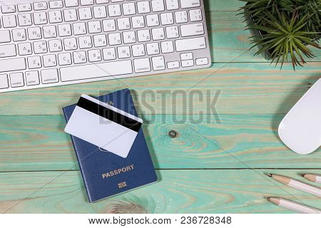 On The Laptop Desk Foreign Passport Credit Cards A Notebook With A Pen. Travel Background, Tourism A
