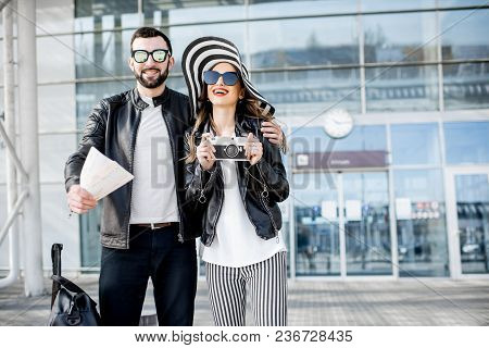 Portrait Of A Young Couple In Leather Jackets Standing With Tickets And Luggage Near The Airport Ter
