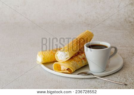 Sweet Dessert. Wafer Tubules With A Delicate Protein Cream And A Cup Of Coffee On A White Round Tray