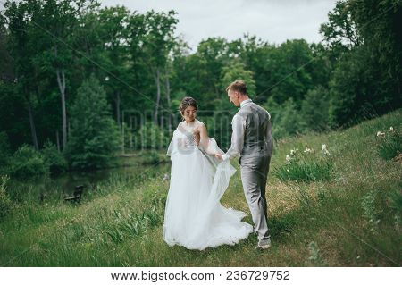Happy Stylish Bride And Groom Walking On The River, Smiling And Kissing