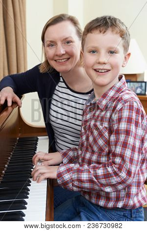 Portrait Of Boy With Music Teacher Having Lesson At Piano