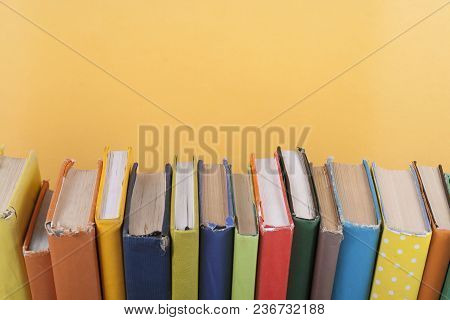 Book Stacking. Open Hardback Books On Wooden Table And Yellow Background. Back To School. Copy Space