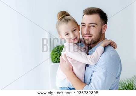 View Of Smiling Father Embracing Cute Daughter
