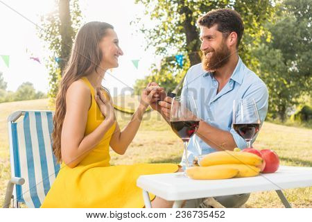 Beautiful young woman accepting with joy and emotion the marriage proposal from her boyfriend during romantic picnic in a sunny day of summer