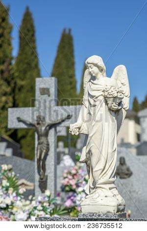 Close-up Of Sculpture In The Shape Of An Angel Placed On A Grave In The Cemetery