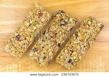 Fruit and nut muesli bar, healthy snack with source of fibre, high in whole grain, no artificial color or flavor, on wood background