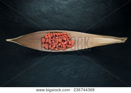Heap Of Dried Goji Berries Placed In Shape Of The Boat Brown And Dry Leaf On Black Stone Background
