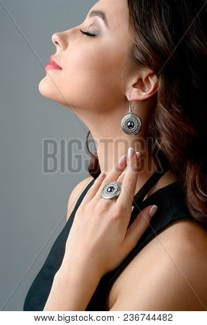 Portrait Of Beautiful Woman With Long Hair Wearing Stylish Silver Jewelery. Necklace And Earring On