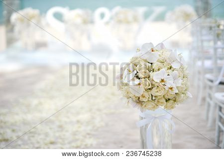 The Beach Wedding Venue Setting With Roses And White Flower On The Transparent Vase Decoration At Th