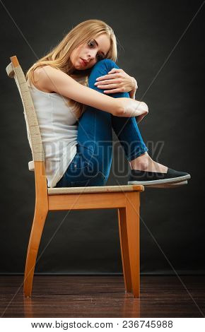 Loneliness Negative Emotion Concept. Young Sad Lonely Woman Sitting Huddled On Chair