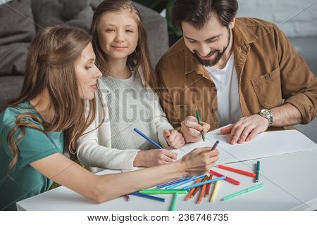 Parents And Daughter Drawing With Felt-tip Pens At Table