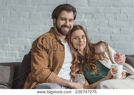 Boyfriend Hugging Girlfriend With Cup Of Tea At Home