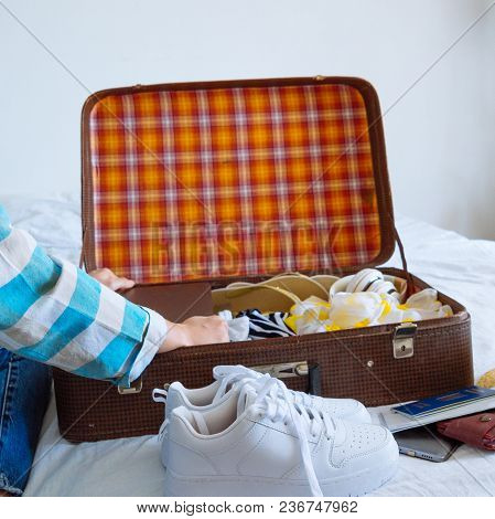 Woman Hands With Watch Put Clothes In Suitcase. Travel Concept. Copy Space