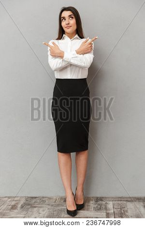 Full length portrait of brunette businesswoman 20s in white shirt and black skirt pointing fingers aside on copyspace with crossed arms isolated over gray background