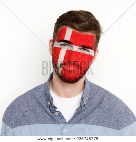 Face Of Young Man Painted With Flag Of Denmark. Football Or Soccer Team Fan, Sport Event, Faceart An