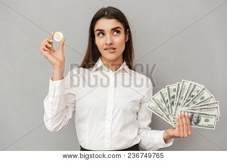 Portrait of caucasian brunette woman with long brown hair in business wear holding bitcoin and lots of money dollar bills isolated over gray background
