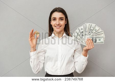 Portrait of smiling successful woman in white shirt and black skirt holding bitcoin and lots of money dollar bills isolated over gray background