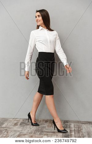 Full length portrait of beautiful businesswoman 20s with long brown hair in white shirt and black skirt walking with smile isolated over gray background